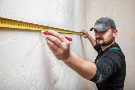 professional builder measures the distance of the tape measure