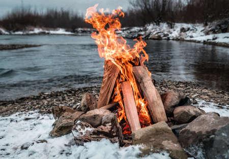 campfire on the winter snowy river bank 版權商用圖片