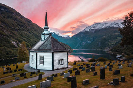 classical Norwegian church in Geiranger over fjord on beautiful red sunset