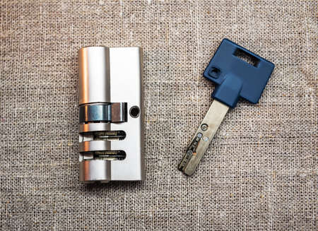 Door cylinder with keys on burlap texture. Locksmith theme 版權商用圖片