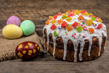 Traditional Easter cake (kulich) and colored eggs on wooden background 版權商用圖片