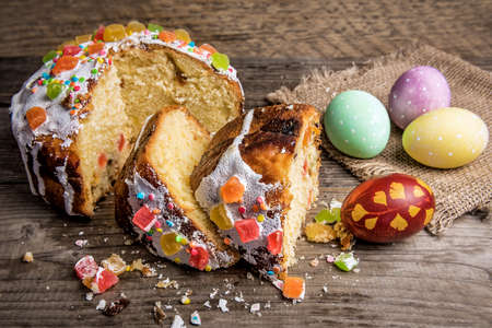 Pieces of traditional Easter cake and eggs on wooden background