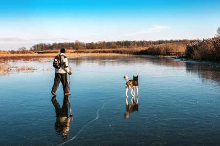 Fisherman and his dog (husky) on ice. Beautiful winter weather