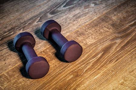 pair of dumbbells on wooden gym floor