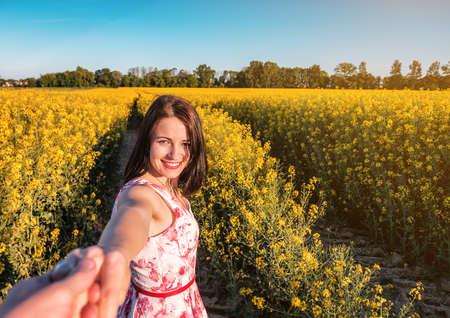 follow me with beautiful girl in yellow rape field