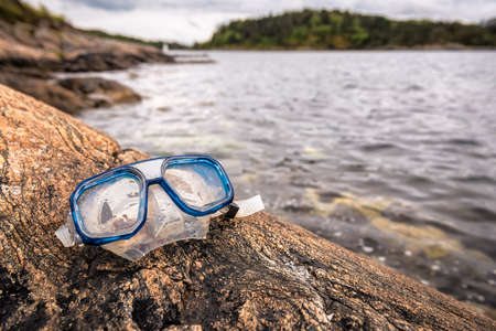 diving, snorkeling mask on the rock on the sea shore