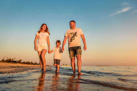 father, mother and young boy are walking at the beach on sunset 版權商用圖片
