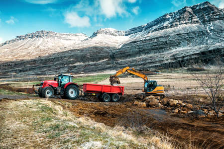 excavator loads stones on tractor trailer
