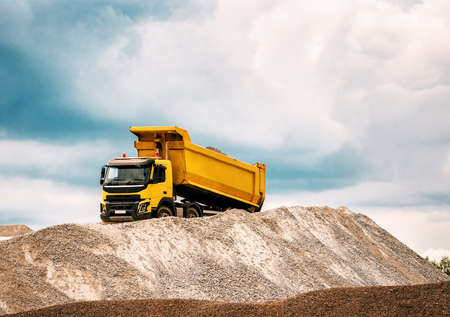 Delivery of sand to the construction site by yellow truck with raised body 版權商用圖片