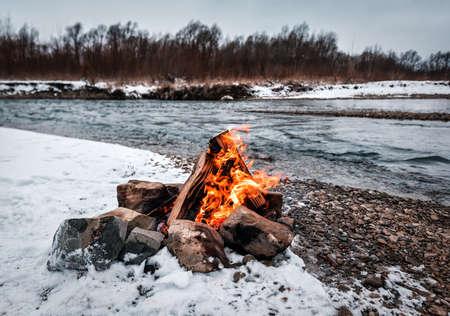 cozy fireplace campfire on the winter river bank 版權商用圖片