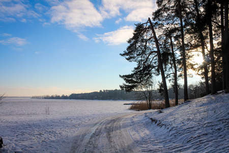 Icy road curve next to the frozen lake. Since there have been strong winds, the surface is very slippery. Foto de archivo