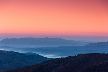 gradual: Beautiful landscape at dawn. Layers of mountain in pink light. Stock Photo