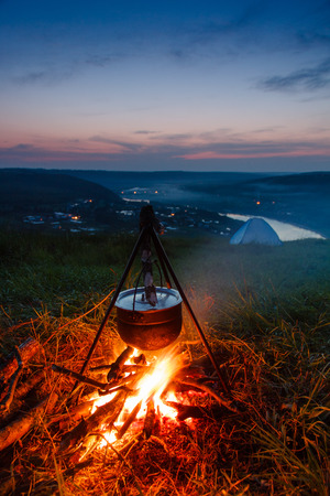 boiling pot: Boiling pot at the campfire on picnic at sunset. Cooking in field conditions. Stock Photo