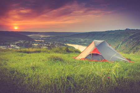 Tourist tent on green meadow at sunset. Camping background. Freedom concept. Filtered image: cross processed vintage effect.
