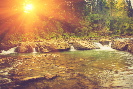 Beautiful landscape of rapids on a mountains river in sunrise. Filtered image: vintage effect.