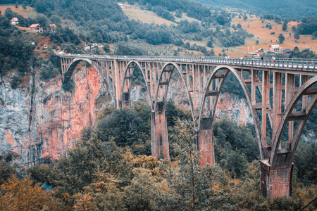 View of the old concrete arch Bridge Djurdjevica Tara in Montenegro. Vintage effect.