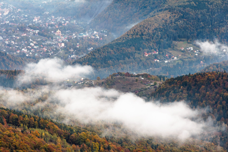 coatings: Landscape in autumn mountains. View from the top of the mountain on the forest fog coatings and village in the valley. Carpathians. Europe.
