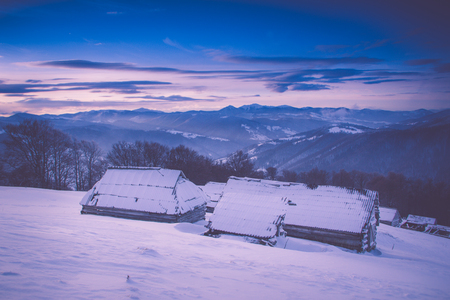 Colorful winter sunrise in the mountains. Fantastic morning glowing by sunlight. View of the snowy forest and old wooden hut cabin. Happy New Year! Filtered image: cross processed retro effect.