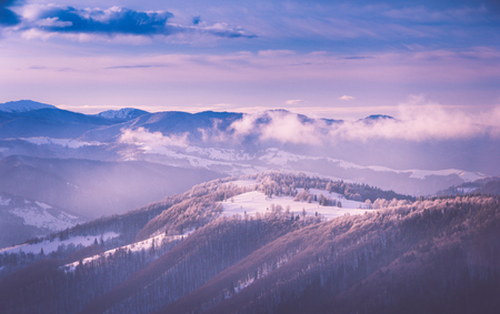 Panoramic view of the winter mountains at sunrise. Landscape with foggy hills. Happy New Year! Filtered image: cross processed retro effect. Stock Photo