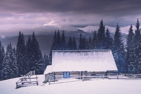 Landscape of winter mountains. View of the snowy forest and old wooden hut cabin. Stock fotó