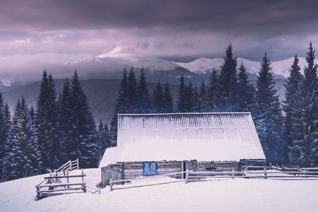 Paisagem de montanhas de inverno. Vista da floresta nevado e da cabine de madeira velha da cabana. Foto de archivo - 93387138