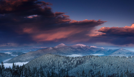 Panoramic view of the dramatic sunset in the winter mountains. Wooded hills covered with snow, fog rising from valleys, colorful cloudy sky - this is impressive picture.