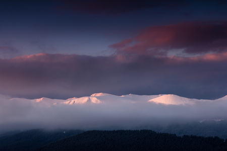Fantastic landscape of winter mountains at sunrise. View of the dramatic cloudy sky and snow-capped peaks in the distance.