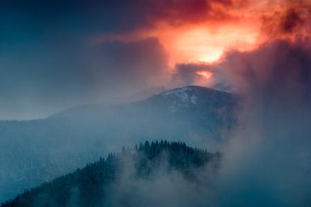Paisaje de la espectacular puesta de sol en la montaña de invierno. Colinas boscosas cubiertas de nieve, niebla saliendo de los valles, cielo nublado colorido: esta es una imagen impresionante. Foto de archivo - 91595092