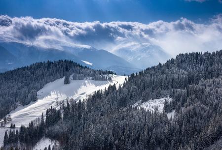 Paisaje de montañas de invierno con mucha nieve en día soleado. Pintoresca y hermosa escena invernal. Vista de las colinas del bosque cubiertas por la nieve y la escarcha. Foto de archivo - 92557388