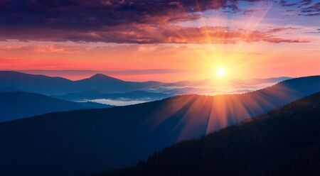 Panoramic view of colorful sunrise in mountains. Concept of the awakening wildlife, romance, emotional experience in your soul, joy in mundane life.
