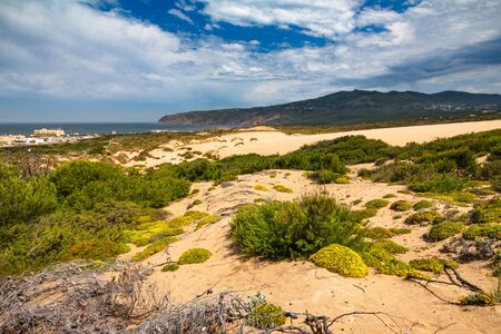 View of sand dunes on the Guincho beach near Atlantic coast. Landscape of sunny day, blue sky and a mountain in background. Cascais. Portugal.
