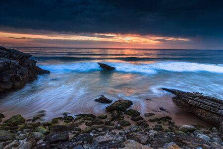 Beautiful sunset on the ocean. Guincho Beach on Atlantic coast near Lisbon. Portugal.