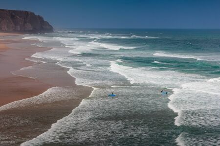 View of the Guincho beach near Atlantic coast. Surfer on the ocean coast with surfboard. Landscape of sunny day, blue sky and a mountain in distance. Cascais. Portugal.
