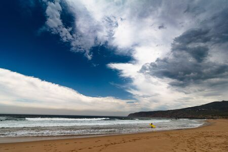 View of the Guincho beach near Atlantic coast. Surfer on the ocean coast in a wet suit with surfboard. Landscape of sunny day, blue sky and a mountain in distance. Cascais. Portugal. Reklamní fotografie