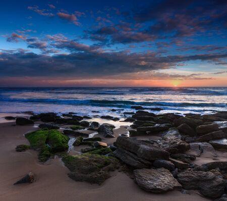 Amazing sunset on the ocean. View of dramatic cloudy sky and stony coastal rocks. Atlantic coast near Lisbon. Portugal.