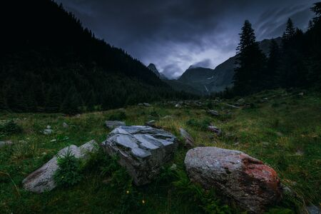 Mysterious and mystical view of the night mountains. Dramatic cloudy sky and mountain peaks in the fog. Fagaras Mountains.Transylvania. Romania.