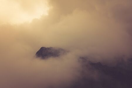 View of morning fog in the mountains. Misty landscape of rocky mountain slopes. Color toning and low contrast. Outdoor travel background.