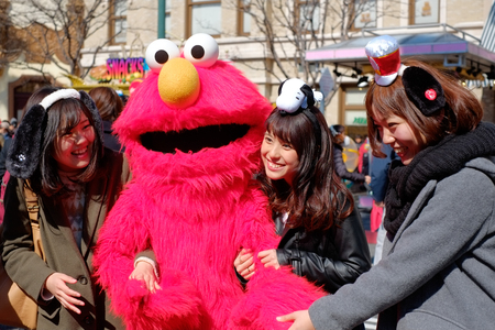 Happy asian girls take shot with Sesame Street Elmo in Universal Studios Japan (USJ), Osaka, Japan