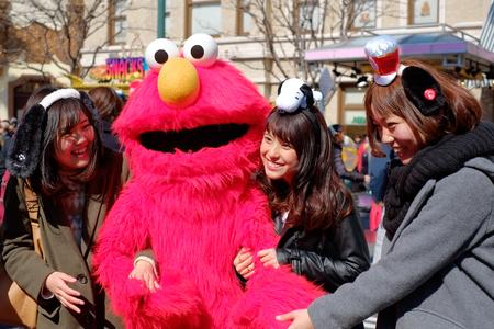 Le ragazze asiatiche felici prendono il colpo con Sesame Street Elmo negli Universal Studios Giappone (USJ), Osaka, Giappone