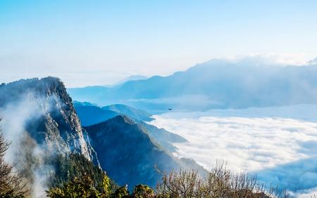 Beautiful morning sunrise, dramatic cloud of sea, giant rocks and Yushan mounatin under bright blue sky in Alishan(Ali mountain) National Park, Taiwan