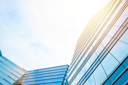 不動産や金融地区には、ビューを - 企業の建設のビジネス概念の高層ビル街のシルエットを反映青い空、太陽の光