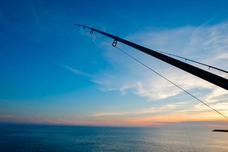 극적인 일몰과 아름다운 바다에서 낚시 극의 실루엣