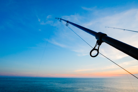 fishing rig: The silhouette of fishing poles under dramatic sunset and beautiful sea