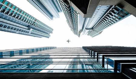 Bedrijfsconcept voor onroerend goed en zakelijke constructie - opzoeken van weergave in financieel district, reflecteren de silhouetten van wolkenkrabbers stad blauwe hemel, zonlicht en vliegtuig