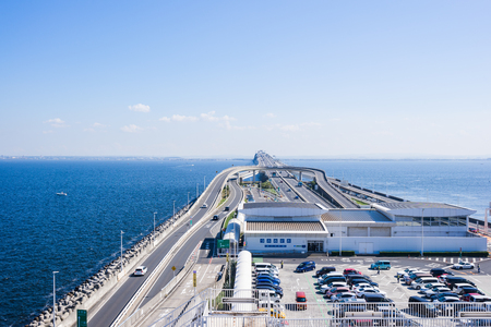 panoramic bird eye top aerial view with beautiful sea level with highway road under dramatic clear glow and fantasy blue sky in Umi Hotaru parking area island Tokyo bay aqua line, Japan