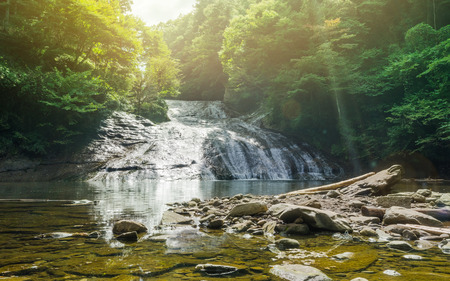 Japan travel concept - beautiful yoro keikoku valley waterfall under dramatic sun glow and morning blue sky in Chiba Prefecture, Japan