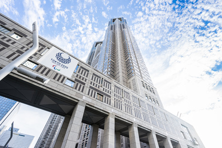 TOKYO, JAPAN - Oct.14 2016: 2020 Olympic concept - looking up view of Tokyo Metropolitan Government Building with Tokyo 2020 Paralympic Games logo, skyscrapers reflect dramatic blue sky and sun lights