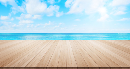 Empty wood table top on blue sea under sunrise and morning bright sky background for display or montage product