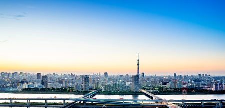 Business concept for real estate corporate construction - panoramic modern city skyline bird eye aerial night view with tokyo skytree under dramatic glow and beautiful dark blue sky in Tokyo, Japan Editorial
