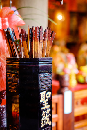Asia culture concept image - fortune sticks in traditional temple, people shake for good future(Chinese Translation on bamboo : fortune sticks) Banque d'images